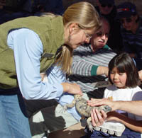 A volunteer helps children collect mineral specimens in egg cartons